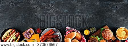 Summer Bbq Food Table Scene With Hot Dog And Hamburger Buffet. Overhead View Bottom Border Over A Da