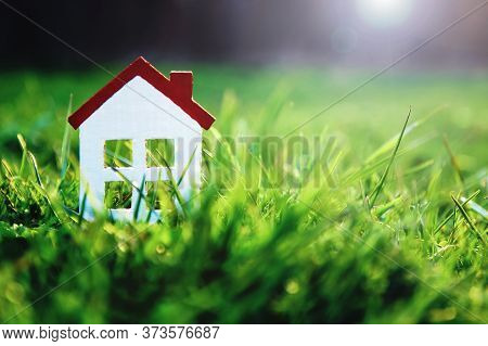 Small White Toy House On Green Grass In Sunshine With Copy Space For Real Estate Purchase, Mortgages