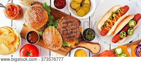Summer Bbq Food Table Scene With Hot Dog And Hamburger Buffet. Top Down View Banner Over A White Woo
