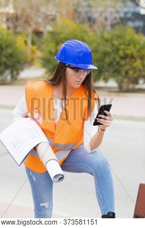 Teenager In Safety Gear Checking Her Phone