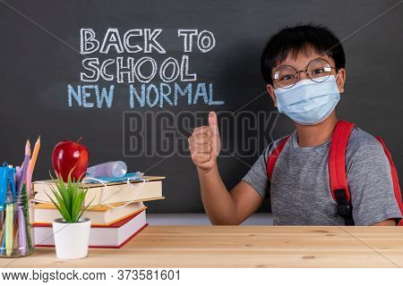 School Boy Wearing Face Mask Thumbs Up Over Blackboard With Text Back To School New Normal. Safe Bac