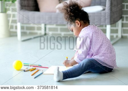 Little African American Enjoy With Writing Or Drawing By Colored Pencils On Notebook Put On The Floo