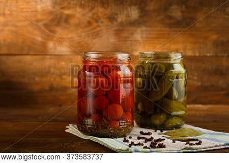Jars Of Pickled Homemade Pickles And Cherry Tomatoes And Sprinkled On A Linen Towel On A Wooden Tabl