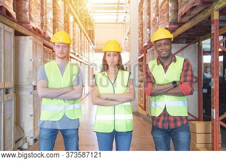 Mixed Raced Caucasian Men And Woman Workers In Safety Hardhat And Safety Uniform Standing With Smile