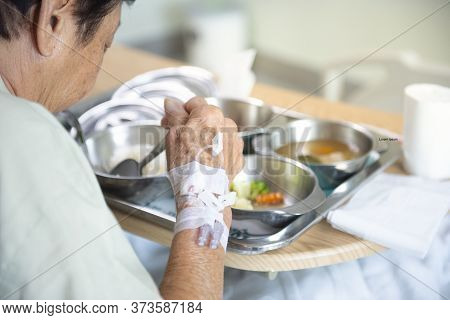 Senior Elder Asian Patient Woman In Hospital Eating Her Lunch On A Tray, Focus On Hand With Injectio