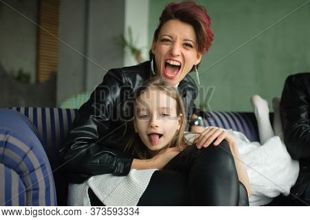 Crazy Mother In Black Leather Jaket And Pants Hugging Her Little Daughter In White Dress, They Are L