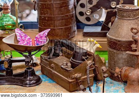 Vintage Telephone, Scales And Milk Pail Surrounded By Other Items From Yesteryear On Display