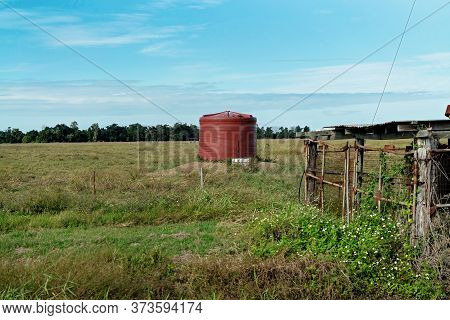 A Red Tank Stand In A Country Paddock For Watering Stock