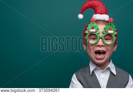 Portrait Of Happy Cheerful Boy Wearing Headband With Santa Claus Hat And Funny Glasses With Christma