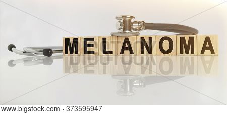 Melanoma The Word On Wooden Cubes, Cubes Stand On A Reflective White Surface, On Cubes - A Stethosco