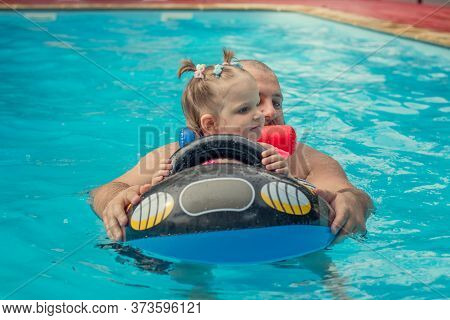 A Happy Cute Little Girl In A Colored Swimsuit Swims With Her Dad In A Pool With An Inflatable Ring.