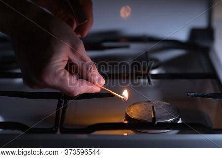 A Man Lights A Gas Stove With A Match, Close-up. Gas Ignition