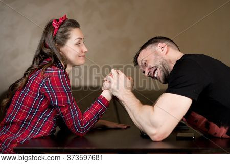 A Man And A Woman Fight On Their Hands, Solving A Family Problem. The Man Is Obviously Stronger, But