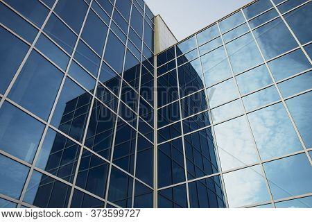 Modern Office Building With Glass Windows And Blue Sky. Dark Blue Texture Of High-rise Buildings. Ab