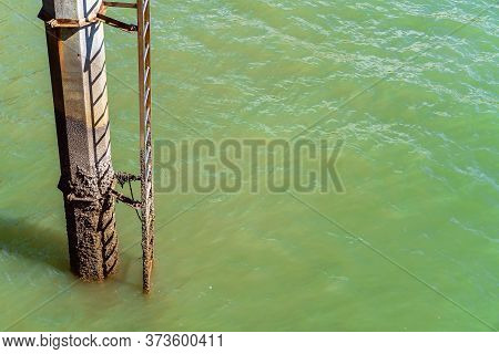A Concrete Scaly Post And A Steel Ladder From A Jetty Down Into The Ocean