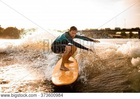 Active Young Athletic Man Wakesurfing Down The River Waves.