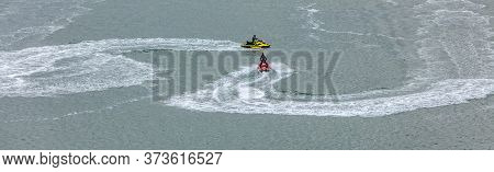 Red Jetski Moving Towards A Yellow Jetski Leaving White Trace Behind It. Sports, Competition Concept
