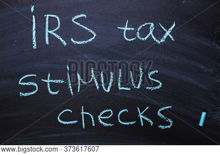 Irs Tax Stimulus Checks Is Written In Chalk On A Blackboard.
