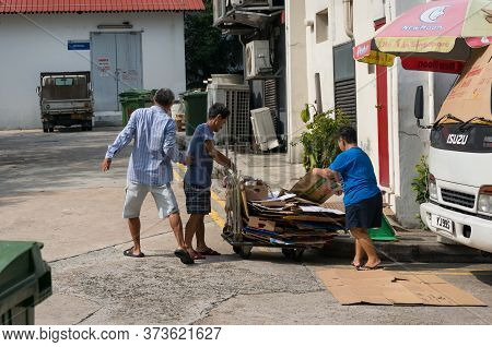 Singapore, Singapore - December 23, 2015: People Collecting Paper Waste For Recycling In Singapore