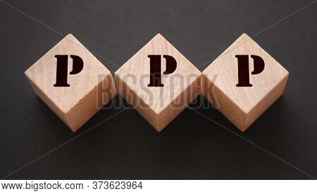 Concept Word Ppp On Wooden Cubes On A Blue Background. Technology Concept