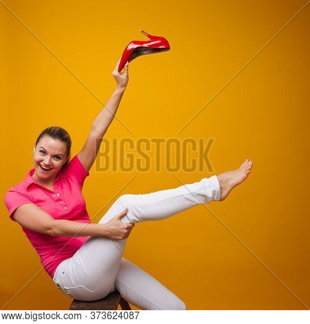 Young Woman Took Off Her Stiletto Shoes And Happy Freedom Foot, Yellow Background