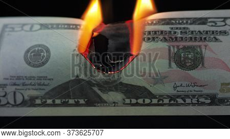Burning Dollar, Global Financial Crisis And Inflation, Concept. Money Banknote On A Black Background