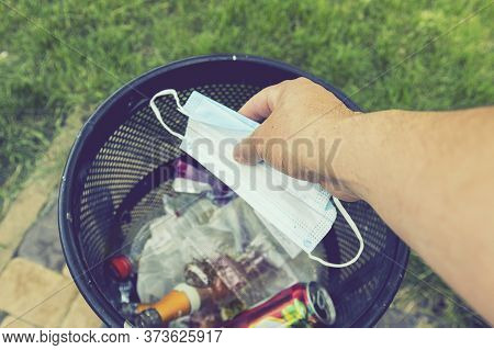 Man Throwing Face Masks Into Trash In Park. Man Throwing Used Surgical Mask Into Recycling Bin. Wast