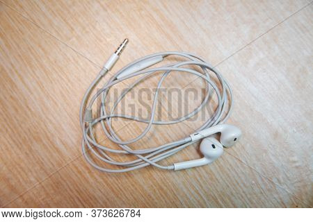 White Earphones From The Phone . Earbud Or Earphone Top View On Wooden Background .