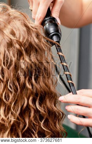Process Of Making Curls By Curling Iron In Hairdressing Salon.