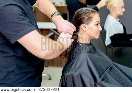 Womens Haircut. Young Woman Receiving Haircut By Male Hairdresser In Hair Salon.