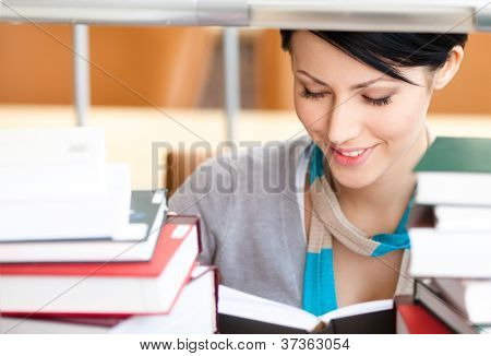 Reading book female student surrounded with piles of books at the library. Studying process
