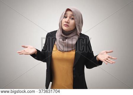 Portrait Of Asian Muslim Businesswoman Wearing Hijab Shows Refusal Or Denial Gesture, Shoulder Shrug