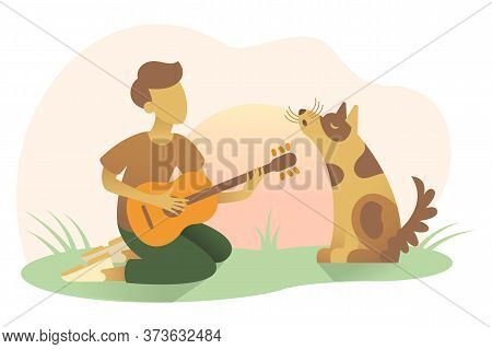 A Boy Plays Guitar And Sings At Sunset Outdoor Sitting On The Grass. A Dog Sits Nearby Its Owner And