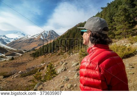 A Long-haired Young Man In A Red Down Jacket And Grey Cap In Sunglasses Stands With His Back To The