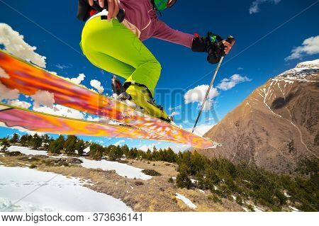 Girl Skier In Flight After Jumping From A Kicker In The Spring Against The Backdrop Of Mountains And