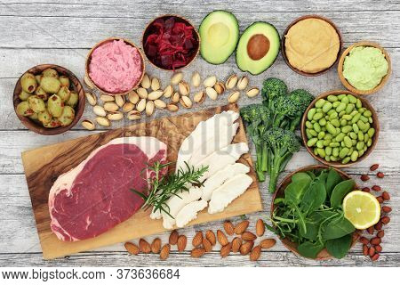 Health food for vitality, energy & fitness with meat, fruit, vegetables, legumes and dips. High in protein, vitamins, minerals, anthocyanins, antioxidants, smart carbs, protein & omega 3. Flat lay.