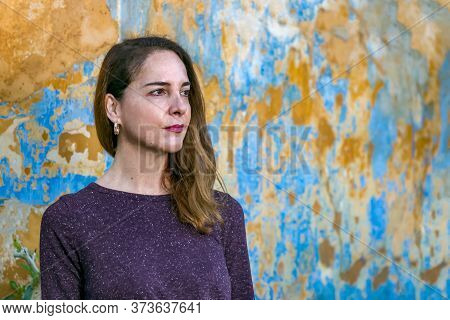 Portrait Of A Beautiful Mature Woman Looking Away Over A An Old Wall Background, Pensive, Thoughtful