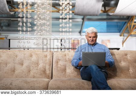 Senior Business Owner Working With Laptop In His Restaurant