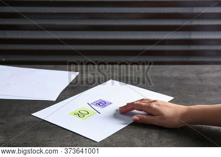 Woman Taking Paper Sheet With 80/20 Rule Representation At Grey Table, Closeup. Pareto Principle Con
