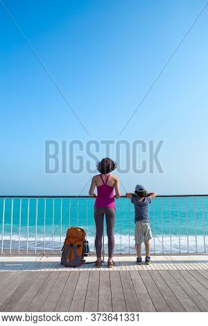 A Boy With His Mother Stand On The Promenade And Look At The Sea. A Woman Walking With Her Son On A