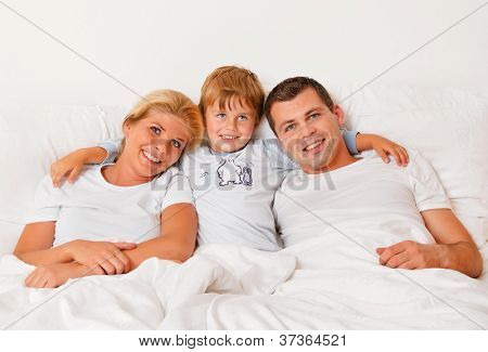 a family is in the morning in bed and having fun