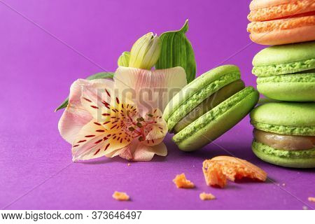French Cookies Close-up , Few Green And Yellow French Macaroons And An Alstroemeria Flower On A Purp