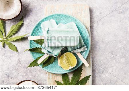 Ice Cream Popsicle Bars With Coconut Slices, Cannabis On Concrete Background. Hemp Ice Cream Popsicl