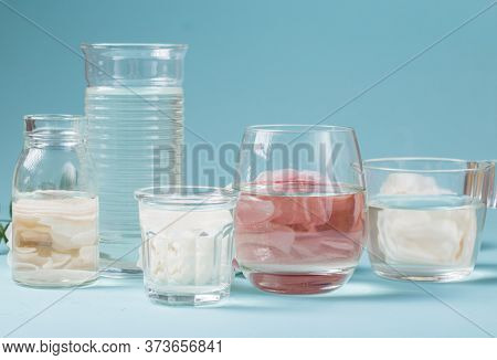 Spring Fresh White, Pink Roses Distorted Through Liquid Water Of  Glass On Blue.
