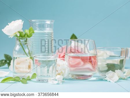 Spring Fresh White, Pink Roses Distorted Through Liquid Water Of  Glass On Blue. Rose Distorted Thro