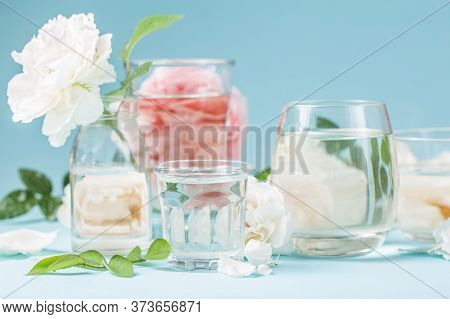 Spring Fresh White, Pink Roses Distorted Through Liquid Water Of  Glass On Blue.branches Distorted T