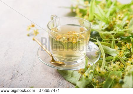 Glass Of Herbal Tea With Linden Flowers.  Tea From Linden. Fresh Flowering Linden On A Wooden Backgr