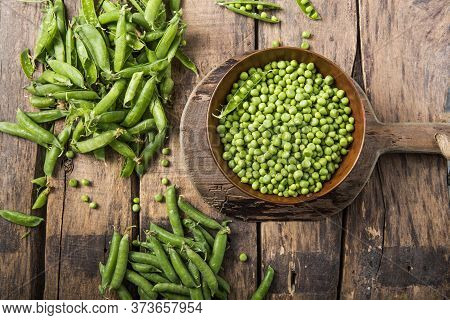 Young Fresh Green Peas On Wooden  Table Viewed From Above. Green Pea Pod Table Peas. Closeup Of Fres