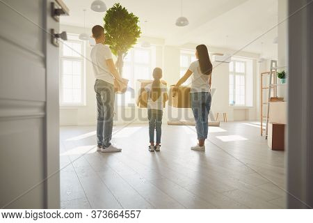 Happy Family With Children Moving With Boxes In A New Apartment House. Back View.