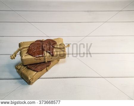 Small Delivery Box Tied With Twine With A Wax Seal On Wooden Boards. Concept: Free Delivery, Gifts,